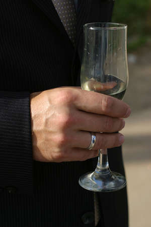 Glass of champagne in a hand of the groom photo