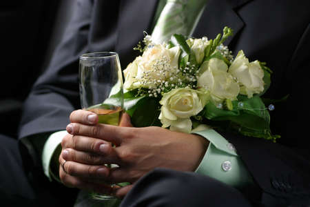 Wedding bouquet and glass with champagne in hands of the groom photo