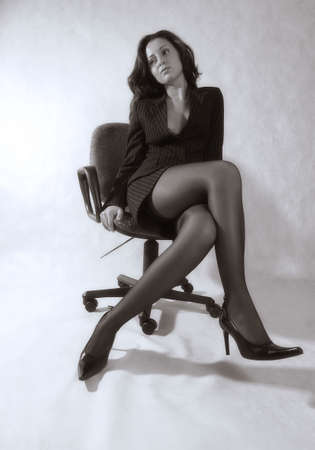 The business woman in office armchair. bw+blue tone photo