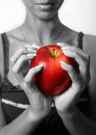 The girl holds in hands red an apple. Partial decolouration