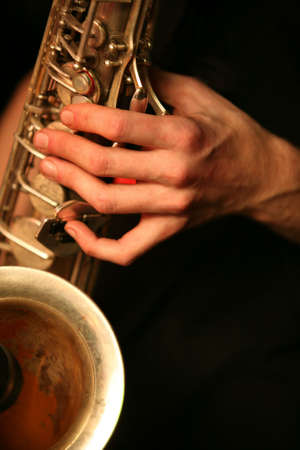 Hands of the saxophonist with a saxophone on a black background