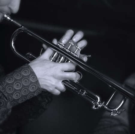 melodies: Trumpet player. Focus on the finger of the saxophone player. bw+blue tone Stock Photo