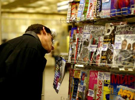 consider: The man chooses magazine Stock Photo