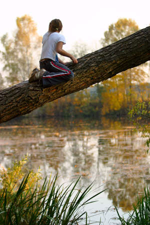 highly: The child sits highly on a tree