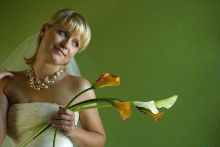 calas blancas: Cinco andamp, ntilde, allas en manos de la novia hermosa en un fondo verde Foto de archivo
