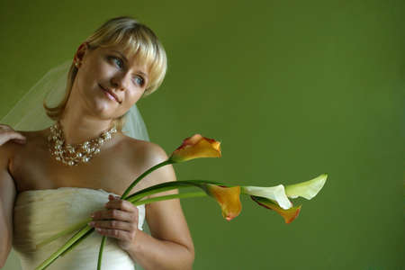 Five andamp,ntilde,allas in hands of the beautiful bride on a green background photo