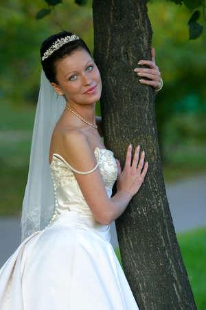 Portrait of the beautiful bride worth near a tree Stock Photo - 683146
