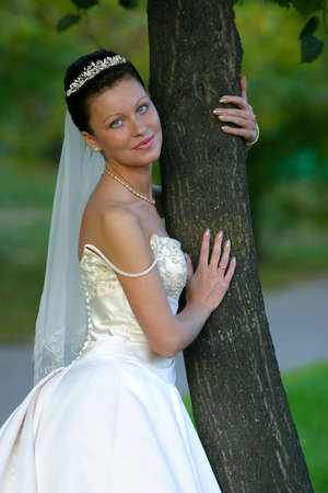 debutante: Portrait of the beautiful bride worth near a tree Stock Photo