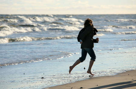 barefooted: The barefooted girl runs on seacoast Stock Photo