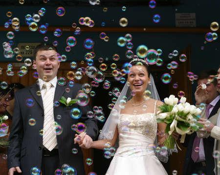 Happy neu verheiratetes Paar vor dem Hintergrund von Seifenblasen