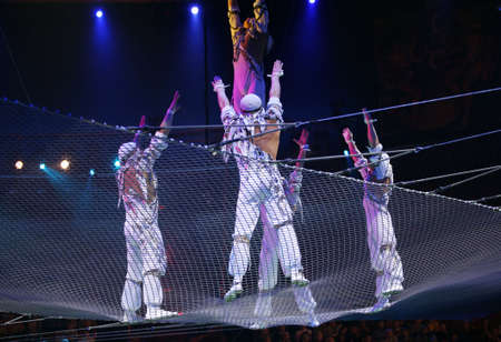 trapeze: Two air acrobats carry out dangerous exercise under a dome of a circus