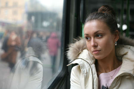 The sad beautiful girl looks in a window of the bus Stock Photo
