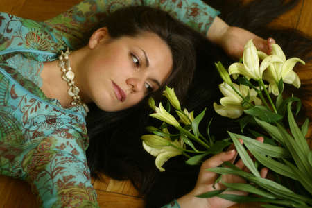 The girl lays on a floor, the sight is inverted to a bouquet from lilies Stock Photo - 753566