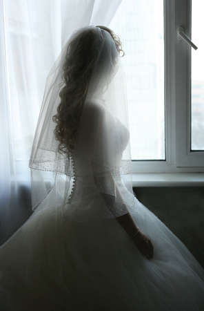 elation: The beautiful bride prepares for wedding. Silhouette on a background of a window Stock Photo
