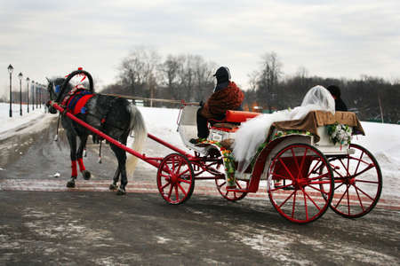 The groom and the bride in a vehicle with red wheels photo