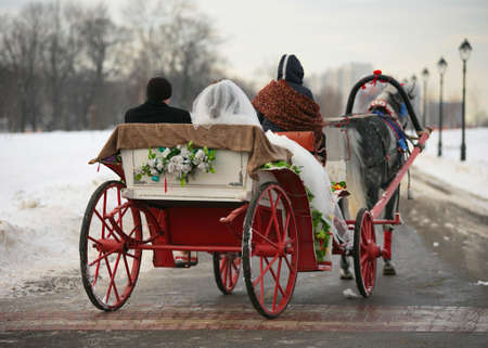 winter wedding: The groom and the bride in a vehicle with red wheels