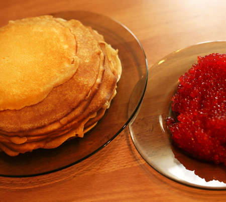Pile of pancakes and caviar on transparent plates photo