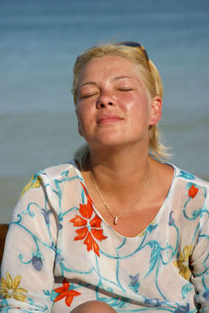 blindly: The woman blindly sunbathes on a background of the sea
