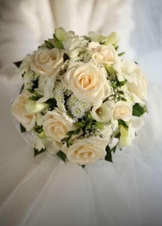 Wedding Bouquet aus beige Rosen auf dem Hintergrund eines Hochzeitskleid