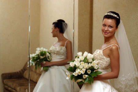 debutante: The beautiful bride with a wedding bouquet from white tulips with reflection in a mirror