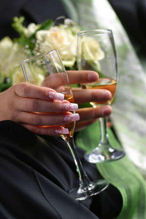 Glass of champagne in a hands of the groom and bride photo