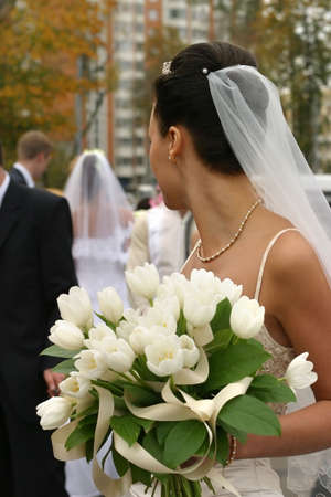 elation: The bride with a bouquet from white tulips looks following to a newly-married couple