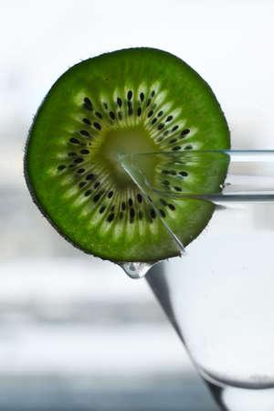 Glass with a plate kiwi on a dim background photo