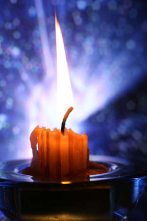 The image of burning candle on a dark blue abstract background photo