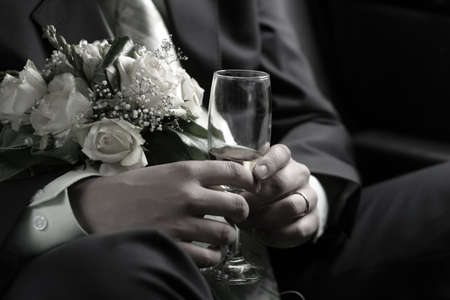 Wedding bouquet and glass with champagne in hands of the groom Stock Photo - 828214