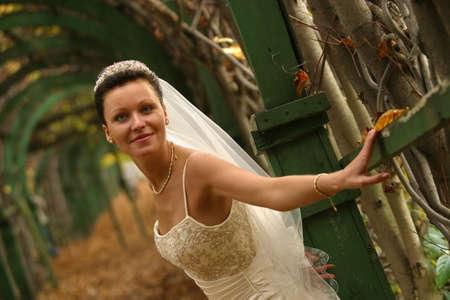 debutante: The beautiful smiling bride one in park