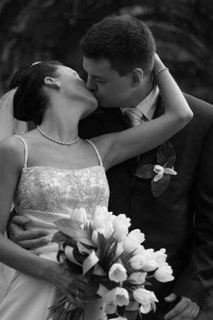 debutante: Beautiful the bride and the groom kiss in park