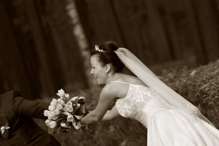 debutante: Beautiful the bride and groom with a bouquet from tulips in park