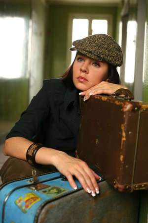 sits: The beautiful woman in a cap sits with two suitcases Stock Photo