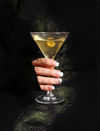 The image of a glass from martinis in a female hand on a black background photo
