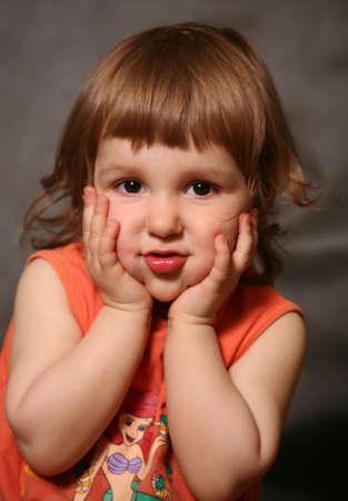 Portrait des zwei-Jahr-alten M�dchens, das H�nde f�r das Gesicht sich benimmt