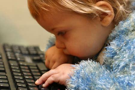 considers: The little boy considers keys of the keyboard