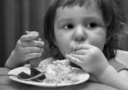 El pequeño niño come macarrones con chorizo. B / w  Foto de archivo - 868613