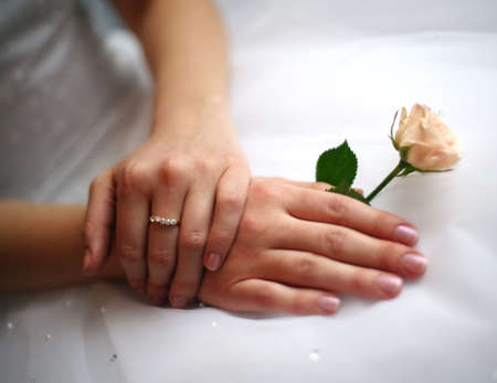 Hands of the bride with a ring and a small rose photo