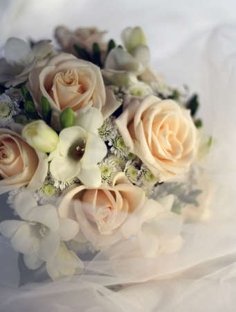 Wedding bouquet from beige roses in a veil Stock Photo