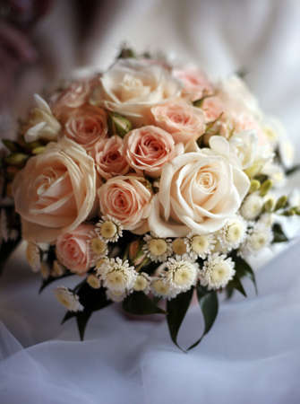 Wedding bouquet from roses and chrysanthemums on a background of a dress