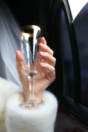 Glass with champagne in a hand of the bride photo