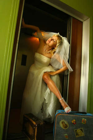 elation: The beautiful bride in the lift with two suitcases