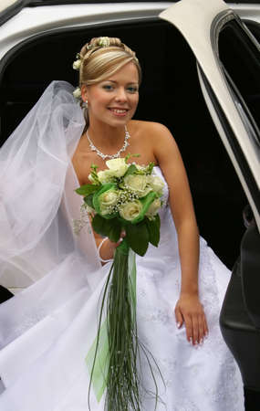 debutante: The beautiful bride with a bouquet in the automobile