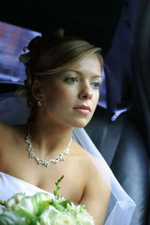 The beautiful bride with a bouquet in the automobile photo