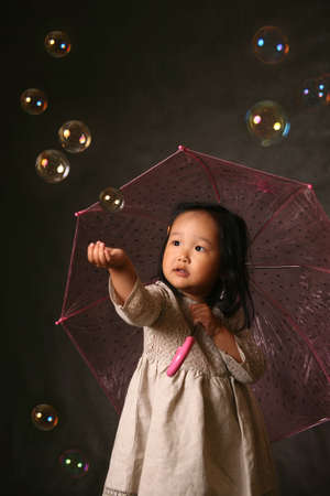 The small Korean girl with a umbrella and soap bubbles Stock Photo