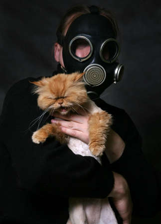 The man in a gas mask holds a shouting red cat photo