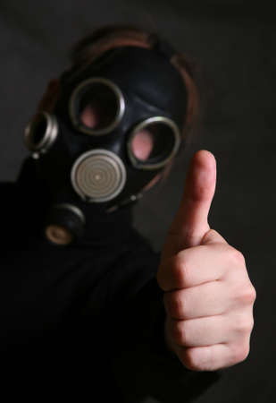The person in a gas mask. A hand in a zone of sharpness the rest is dim photo