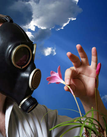 The man in a gas mask with flowers Stock Photo - 1291034