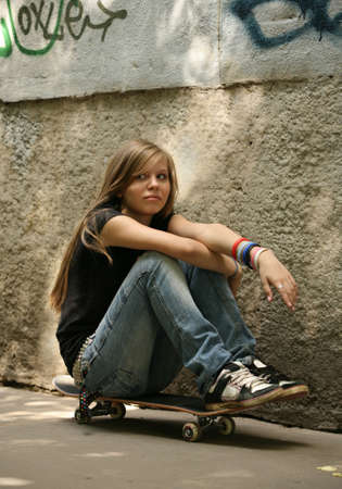 The girl with skateboard sitting against awall Stock Photo - 1291055