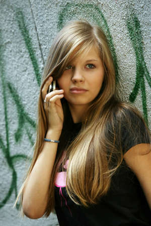 The girl - teenager with the phone on a background of a wall